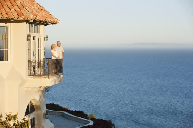 Senior couple on balcony of house overlooking ocean