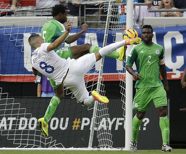 United States's Clint Dempsey (8) takes a shot on goal as he is defended by Nigeria's Efe Ambrose, center, as Joseph Yobo (2) looks on during the first half of an international friendly soccer match in Jacksonville, Fla., Saturday, June 7, 2014. (AP Photo/John Raoux)