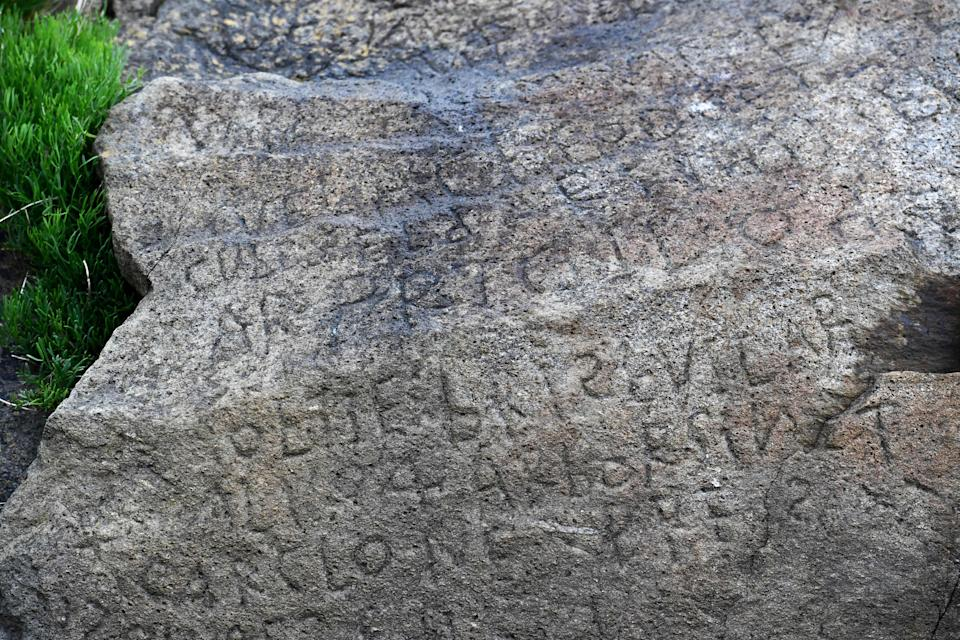 This picture taken on May 7, 2019 shows inscriptions composing indecipherable words on a rock in the Brittany village of Plougastel-Daoulas. The city launched a national call with a 2000 euros reward to anyone able to solve the mystery of those inscriptions probably made during the 18th century. (Photo by FRED TANNEAU/AFP/Getty Images)