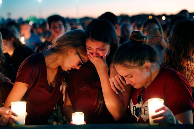 <p>Students console each other as they weep during a candlelight vigil for the victims of the Wednesday shooting at Marjory Stoneman Douglas High School, in Parkland, Fla., Thursday, Feb. 15, 2018. (Photo: Gerald Herbert/AP) </p>