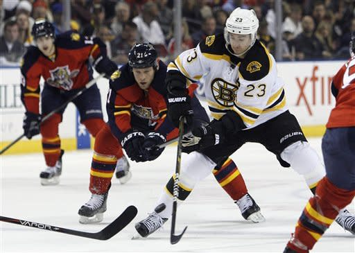 Boston Bruins center Chris Kelly (23) chases the puck with Florida Panthers right wing Krys Barch (21) during the first period of an NHL hockey game, Monday, Jan. 16, 2012, in Sunrise, Fla. (AP Photo/Lynne Sladky)
