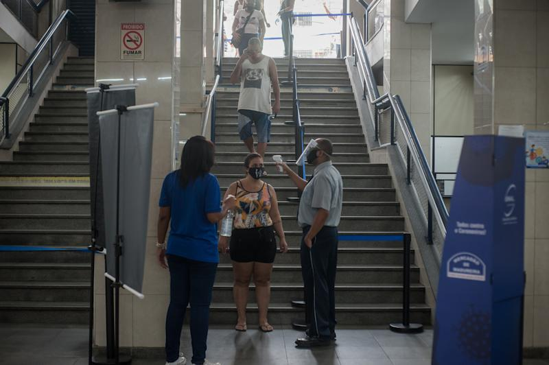 "People are seen during the measurement of temperature and application of alcohol gel in the access to a mall known as ""Mercadão de Madureira"", located in the north of the city of Rio de Janeiro, on June 19, 2020. Local authorities have started the second of six steps to make social isolation more flexible and companies follow safe social distance measures to prevent the spread of COVID-19 (coronavirus), which allows only 30% of capacity in stores (Photo by Allan Carvalho/NurPhoto via Getty Images)"
