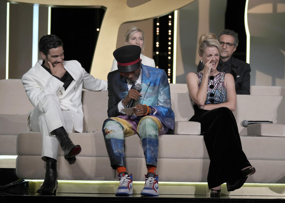 Jury president Spike Lee, bottom center, almost announces 'Titane' as the winner of the Palme d'Or for the second time as fellow jury members Tahar Rahim, bottom left, Jessica Hausner, back left, Melanie Laurent, bottom right, and Kleber Mendonca Filho, back left, look on during the awards ceremony at the 74th international film festival, Cannes, southern France, Saturday, July 17, 2021. (AP Photo/Vadim Ghirda)
