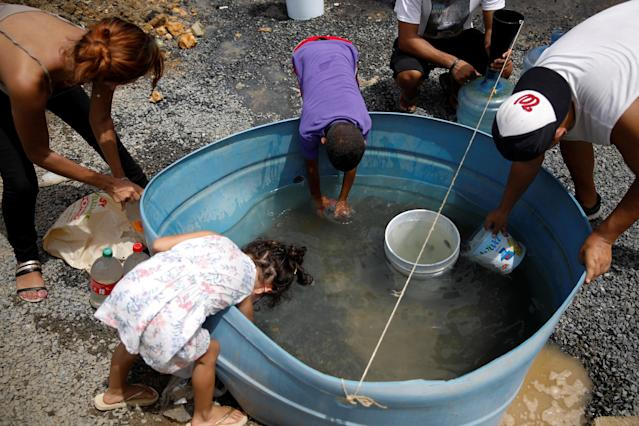 People fill containers with water in Canovanas, Puerto Rico, on Tuesday. (Carlos Garcia Rawlins / Reuters)