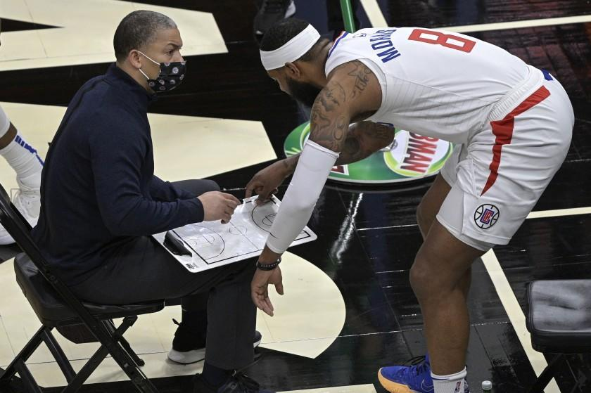 Los Angeles Clippers head coach Tyronn Lue, left, and forward Marcus Morris Sr. (8) discuss a play during a timeout in the second half of an NBA basketball game against the Orlando Magic, Friday, Jan. 29, 2021, in Orlando, Fla. (AP Photo/Phelan M. Ebenhack)