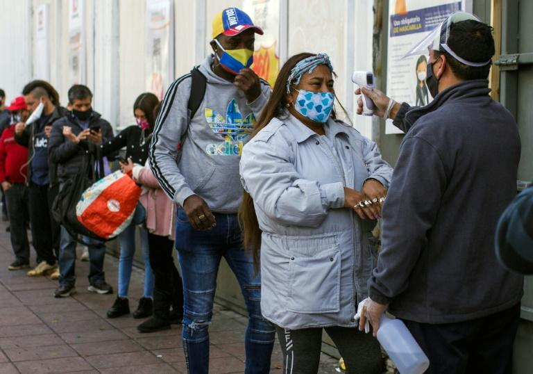 A worker checks the temperature of a customer outside a supermarket in Valparaiso on June 12 as the city went under quarantine