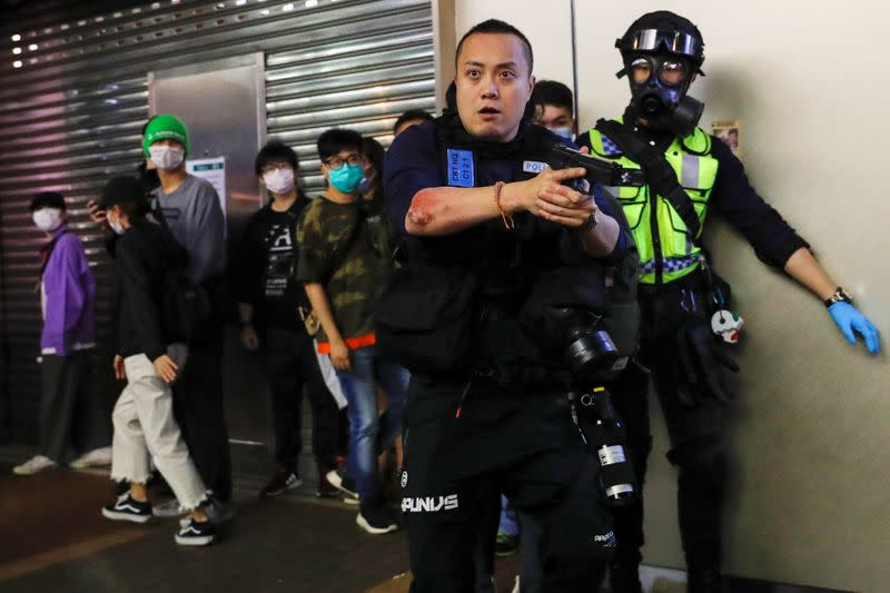A police officers holds his gun as he is surrounded by anti-government protesters after a clash, at Mong Kok, in Hong Kong