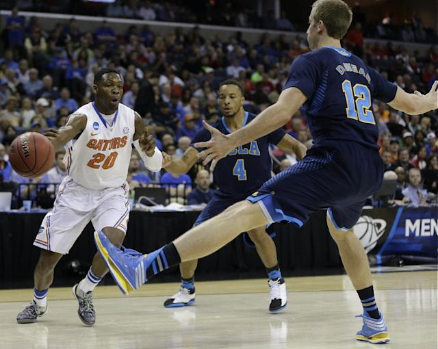 Florida guard Michael Frazier II (20) passes the ball against UCLA forward David Wear (12) during the first half in a regional semifinal game at the NCAA college basketball tournament, Thursday, March 27, 2014, in Memphis, Tenn. (AP Photo/Mark Humphrey)