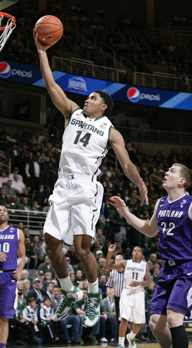 Michigan State's Gary Harris (14) puts up a layup against Portland Ryan Nicholas (32) during the first half of an NCAA college basketball game, Monday, Nov. 18, 2013, in East Lansing, Mich. (AP Photo/Al Goldis)