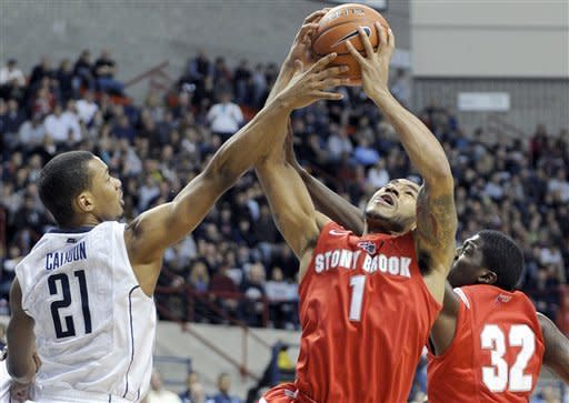 Connecticut's Omar Calhoun, left, attempts to block the shot of Stony Brook's Ron Bracey during the first half of an NCAA college basketball game in Storrs, Conn., Sunday, Nov. 25, 2012. (AP Photo/Fred Beckham)