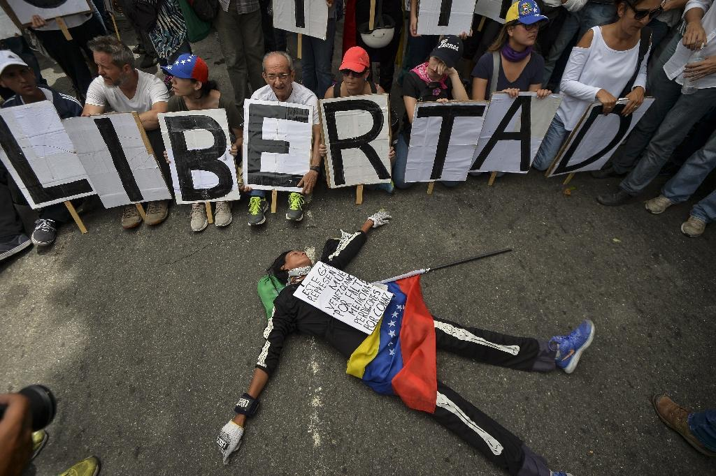 "Opposition demonstrators holding signs spelling ""freedom"" protest during a march by doctors and other health care personnel in Caracas, Venezuela, on May 22, 2017 (AFP Photo/LUIS ROBAYO)"