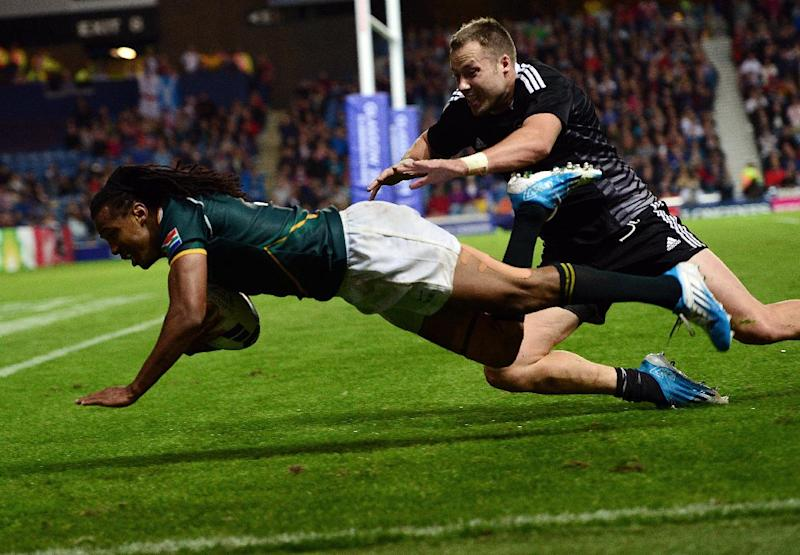 South Africa's Cecil Afrika scores a try during the Commonwealth Games rugby sevens gold medal match against New Zealand in Glasgow on July 27, 2014