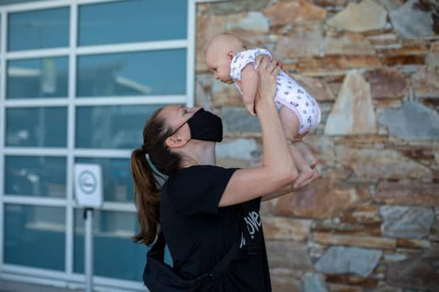 Team Canada basketball player Kim Gaucher, seen above with daughter Sophie at the Vancouver International Airport on Thursday, says she's being forced to choose between the 2020 Tokyo Olympics and breastfeeding her three-month-old daughter due to COVID-19 rules that prevent family from attending the Summer Games. (Ben Nelms/CBC - image credit)