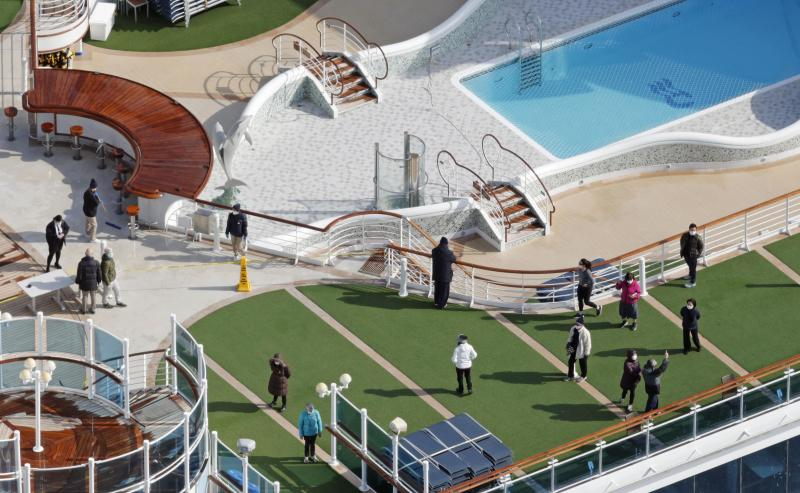 Photo taken from a Kyodo News helicopter shows passengers strolling on the deck of the cruise ship Diamond Princess docked at the port of Yokohama.