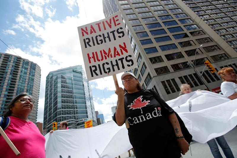 A woman holds a sign as several hundred indigenous people march through the streets of Toronto to bring attention to the plight of indigenous peoples in Canada, on June 24, 2010
