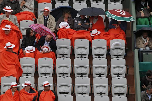 Spectators shield themselves form the rain as they watch the quarterfinal match of the French Open tennis tournament between Romania's Simona Halep and Russia's Svetlana Kuznetsova at the Roland Garros stadium, in Paris, France, Wednesday, June 4, 2014. (AP Photo/Michel Euler)