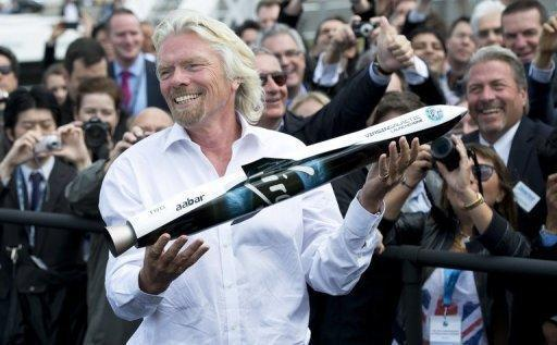 British tycoon Richard Branson poses with a model of Launcher One, an air-launched rocket, to the crowd during a photocall for Virgin Galactic, the world's first commercial spaceline, at the Farnborough International Airshow in Hampshire, southern England, on Wednesday. Branson said he and his family will be the first on board his new Virgin Galactic space tourism programme