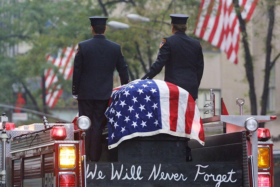 <p>Firefighters stand atop a fire engine with the flag draped casket of fellow fireman Lt. Dennis Mojica September 21, 2001 during a memorial at St. Patrick's Cathedral in New York City. Mojica, who was with Rescue Company 1. </p>