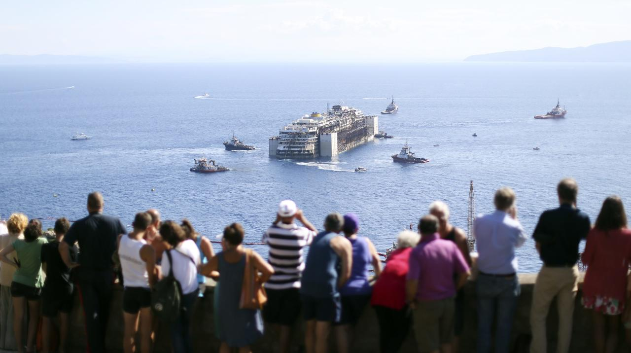 People watch the cruise liner Costa Concordia moving anticlockwise during the refloat operation maneuvers at Giglio Island July 23, 2014. Maneuvers began early on Wednesday to remove the rusty hulk of the Costa Concordia cruise liner from the Italian island where it struck rocks and capsized two years ago, killing 32 people. A convoy of 14 vessels, led by the tug boat Blizzard, will start to tow the Concordia later on Wednesday to a port near Genoa in northern Italy where it is due to arrive on Sunday, before being broken up for scrap.REUTERS/ Alessandro Bianchi ( ITALY - Tags: DISASTER TRANSPORT MARITIME SOCIETY TPX IMAGES OF THE DAY)