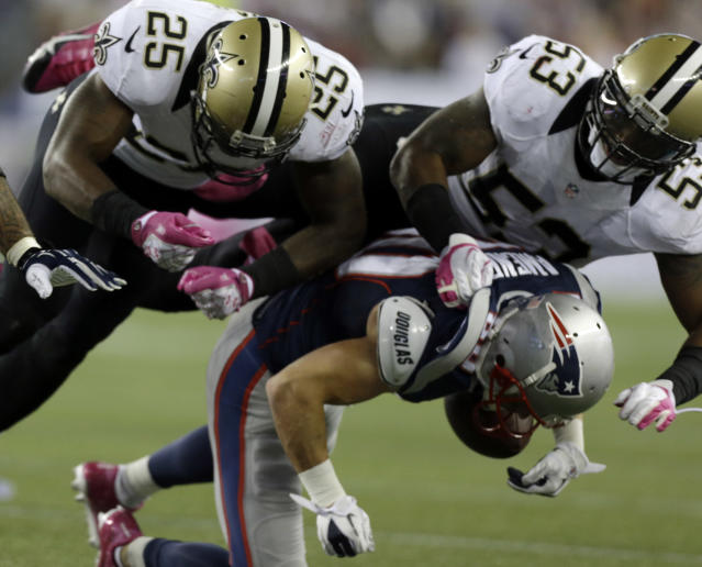 New Orleans Saints defensive back Rafael Bush (25) and linebacker Ramon Humber (53) tackle New England Patriots wide receiver Danny Amendola after a catch in the third quarter of an NFL football game against the New Orleans Saints Sunday, Oct. 13, 2013, in Foxborough, Mass. Amendola was injured on the play. (AP Photo/Steven Senne)