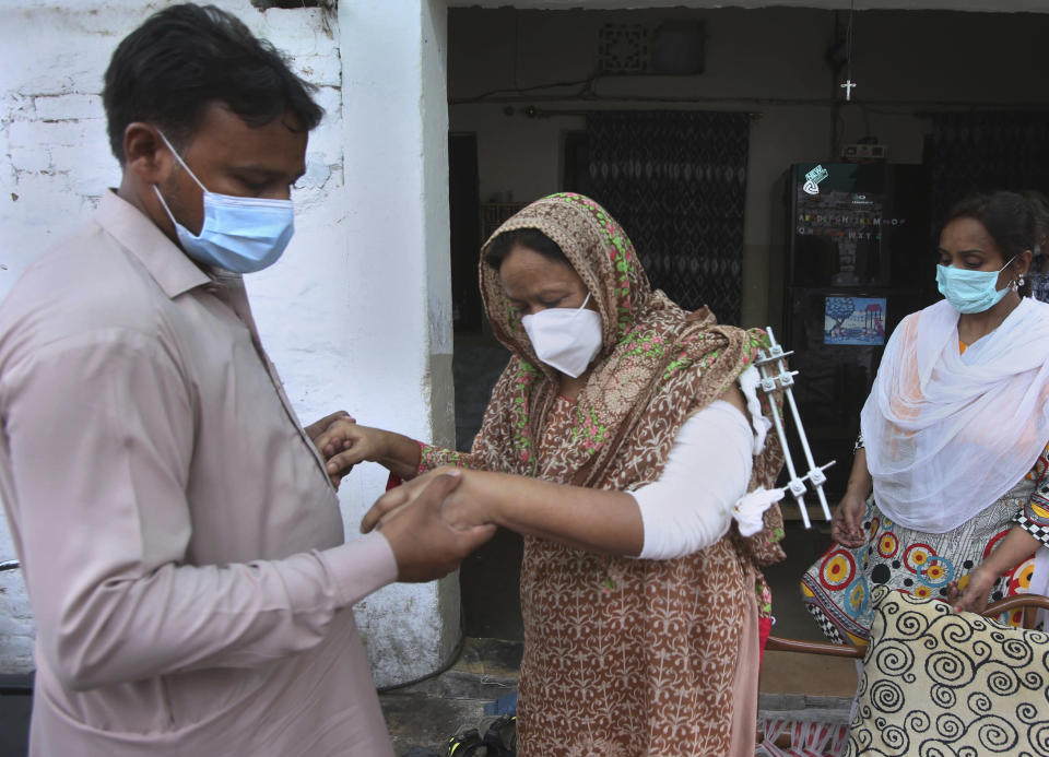 Family members help to Elizabeth Lal, center, who was injured and her son-in-law Nadeem Jordon killed by gunmen because he rented in a Muslim neighborhood, as she arrives for an interview with the Associated Press, in Peshawar, Pakistan, Thursday, July 9, 2020. Analysts and activists say minorities in Pakistan are increasingly vulnerable to Islamic extremists as Prime Minister Imran Khan vacillates between trying to forge a pluralistic nation and his conservative Islamic beliefs. (AP Photo/Muhammad Sajjad)