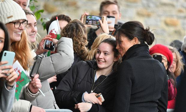Meghan Markle poses with fans to take a photograph together along the crowd sideline