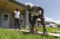 Darrel Duncombe stands nearby as Max Hall cuts a sheet of plywood to use to repair a roof in preparation for the arrival of Hurricane Isaias in Freeport, Grand Bahama, Bahamas, Friday, July 31, 2020. (AP Photo/Tim Aylen)