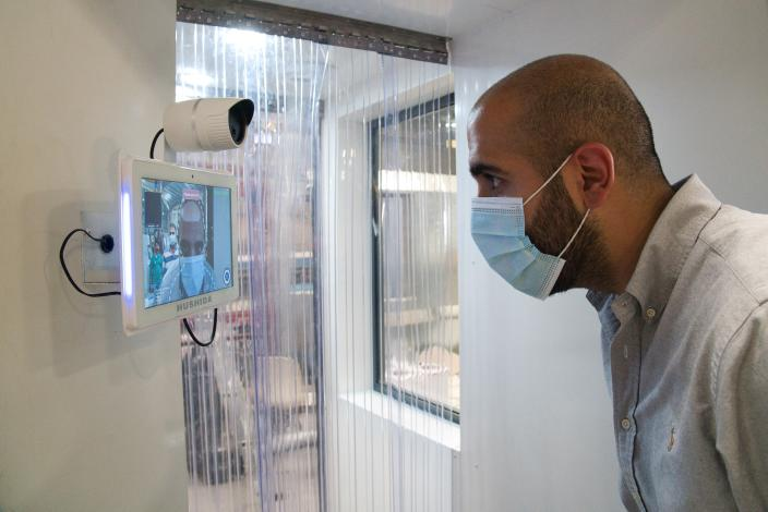 FILE - In this April 27, 2020, file, photo, a worker examines a gate system made by Guard ME that conducts temperature checks and fogs disinfectants on users, in Dubai, United Arab Emirates. Efforts by the United Arab Emirates to fight the coronavirus have renewed questions about mass surveillance in this U.S.-allied federation of seven sheikhdoms. (AP Photo/Jon Gambrell, File)