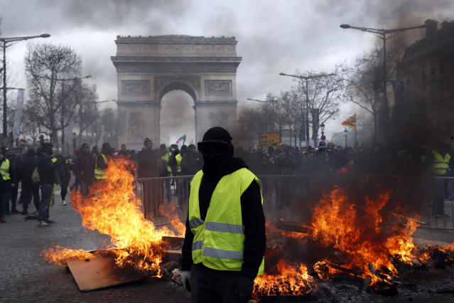 A protester stand in front of a barricade on fire during a yellow vests demonstration Saturday, March 16, 2019 in Paris. Paris police say more than 100 people have been arrested amid rioting in the French capital by yellow vest protesters and clashes with police. They set life-threatening fires, smashed up luxury stores and clashed with police firing tear gas and water cannon (AP Photo/Christophe Ena)