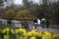People walk past daffodils in St James's Park, amid the coronavirus disease (COVID-19) outbreak in London