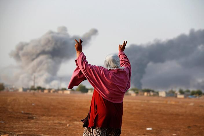 Kiymet Ergun, a Syrian Kurd, gestures as she watches from Mursitpinar, Turkey,  as allied aircraft attack Islamic State targets on Oct. 13 in Kobani, Syria.