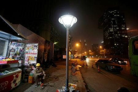 A worker rests outside a construction site at night in Beijing's central business district area, China April 16, 2017. REUTERS/Jason Lee