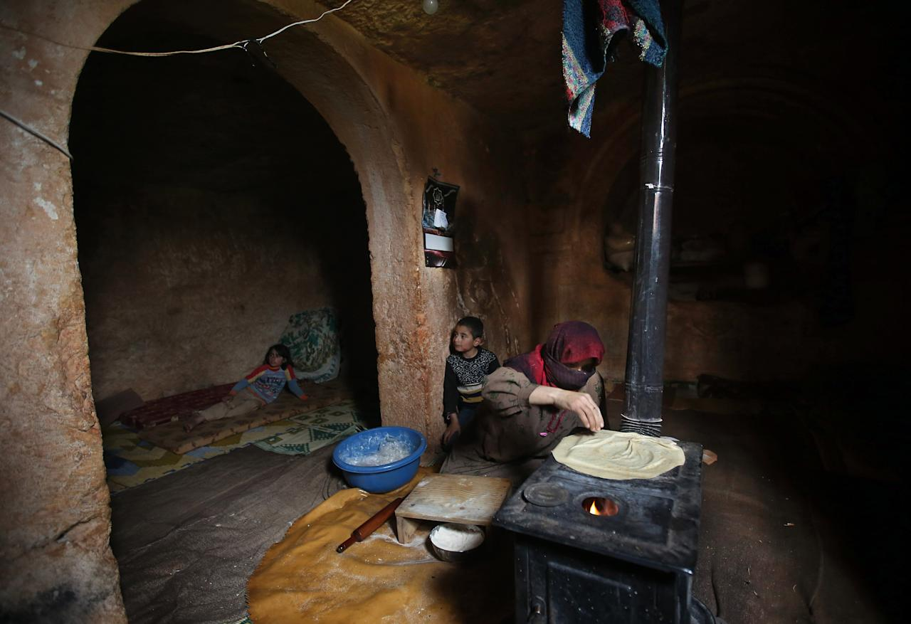 Nadia, 53, makes bread on a wooden stove, at an underground Roman tomb which she uses as a shelter with her family from Syrian governemnt forces shelling and airstrikes, at Jabal al-Zaweya, in Idlib province, Syria, Thursday, Feb. 28, 2013. Across northern Syria, rebels, soldiers, and civilians are making use of the country's wealth of ancient and medieval antiquities to protect themselves from Syria's two-year-old war. They are built of thick stone that has already withstood centuries, and are often located in strategic locations overlooking towns and roads. (AP Photo/Hussein Malla)