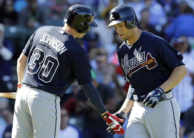 Atlanta Braves' Andrelton Simmons, right, celebrates with Elliot Johnson after hitting a solo home run against the Chicago Cubs during the fourth inning of a baseball game in Chicago, Sunday, Sept. 22, 2013. (AP Photo/Nam Y. Huh)