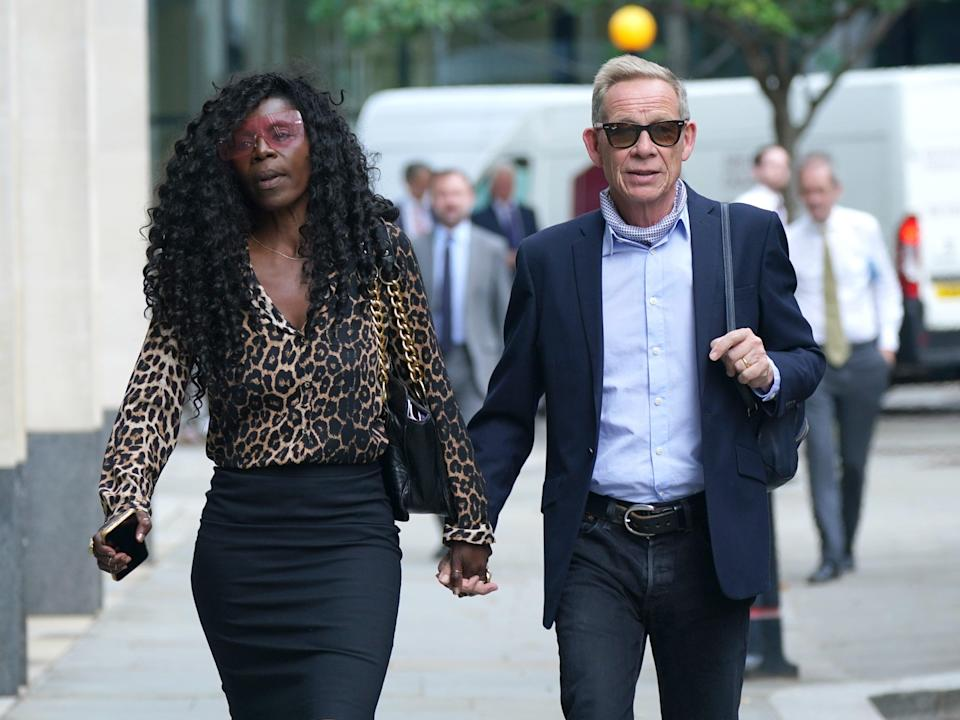 Paul Cook arrives at the Rolls Building at the High Court in London with his wife Jeni (Yui Mok/PA) (PA Wire)