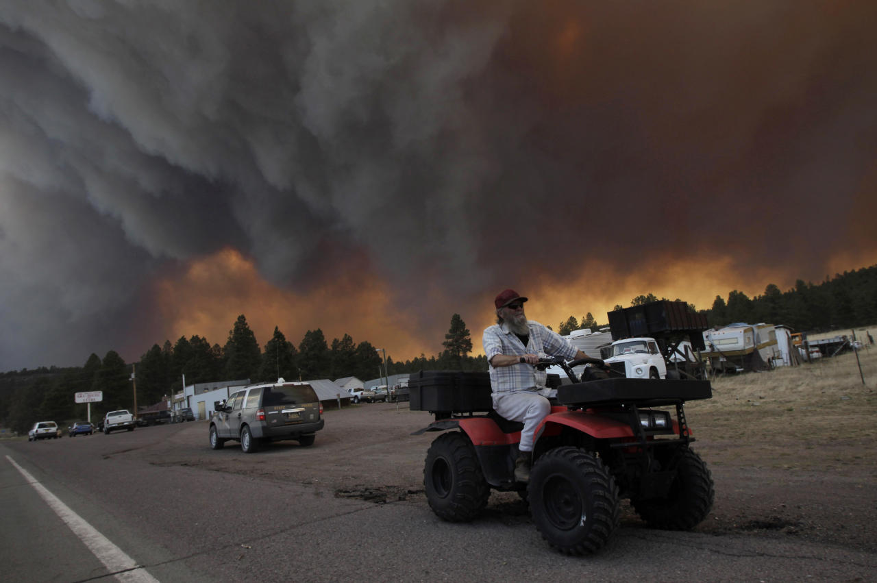 Robert Joseph, 64, rides his ATV as smoke plumes from the Wallow fire fill the sky in Luna, N.M., Monday, June 6, 2011. Firefighters worked furiously Monday to save a line of mountain communities in eastern Arizona from a gigantic blaze that has forced thousands of people from their homes and cast a smoky haze over states as far away as Iowa.