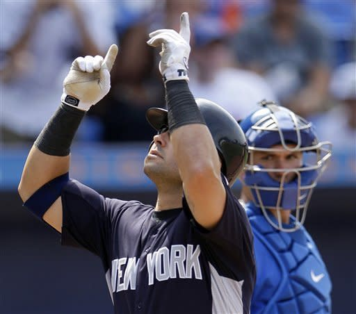 New York Yankees' Nick Swisher, left, gestures as he crosses home plate in front of New York Mets catcher Josh Thole after hitting a solo home run in the fourth inning of a spring training baseball game in Port St. Lucie, Fla., Tuesday, April 3, 2012. (AP Photo/Patrick Semansky)