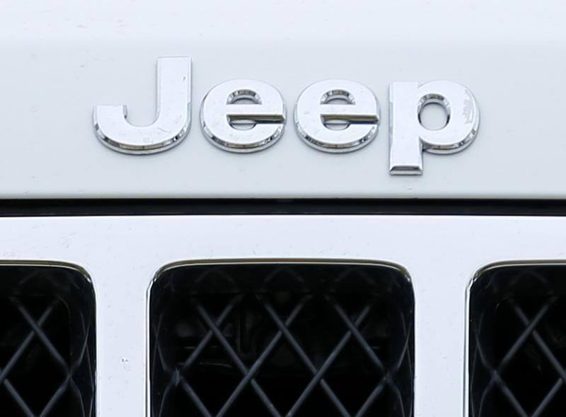 Logo on the front of a Jeep vehicle is shown at Chrysler dealership in Carlsbad, California