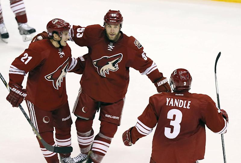 Phoenix Coyotes' Derek Morris (53) celebrates his goal against the Nashville Predators with teammates Andy Miele (21) and Keith Yandle (3) during the second period of an NHL hockey game on Thursday, Oct. 31, 2013, in Glendale, Ariz. (AP Photo/Ross D. Franklin)