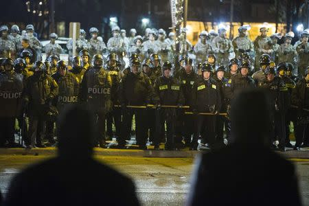 Protesters stare at a line of police officers and National Guard soldiers during a protest to demand justice for the killing of 18-year-old Michael Brown, outside the Ferguson Police Department in Ferguson, Missouri in this file photo taken November 28, 2014.  REUTERS/Lucas Jackson/Files