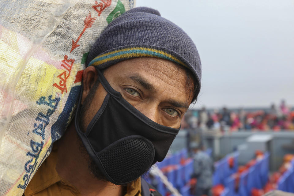 A Rohingya refugee headed to the Bhasan Char island wearing a mask arrives to board a navy vessel from the south eastern port city of Chattogram, Bangladesh, Monday, Feb.15,2021. Authorities sent a fourth group of Rohingya refugees to the newly developed island in the Bay of Bengal on Monday amid calls by human rights groups for a halt to the process. (AP Photo)