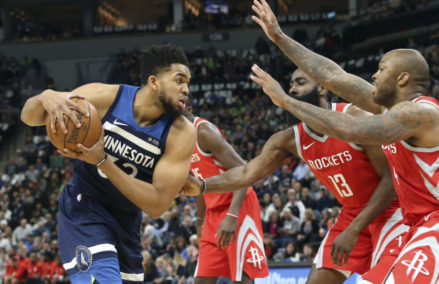 Minnesota Timberwolves' Karl-Anthony Towns, left, is double-teamed by Houston Rockets' PJ Tucker, right, and James Harden in the first half during Game 3 of an NBA basketball first-round playoff series Saturday, April 21, 2018, in Minneapolis. (AP Photo/Jim Mone)
