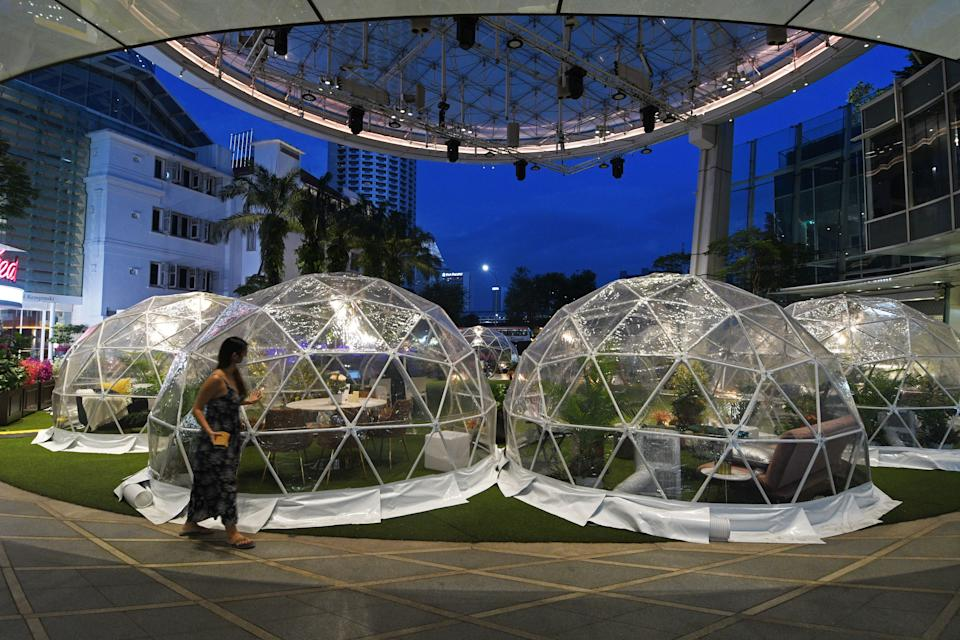 SINGAPORE, Oct. 21, 2020 -- A woman walks past dining domes, installations which help prevent the spread of the COVID-19 epidemic, at Capitol Singapore Outdoor Plaza, Singapore, on Oct. 21, 2020. (Photo by Then Chih Wey/Xinhua via Getty) (Xinhua/Then Chih Wey via Getty Images)