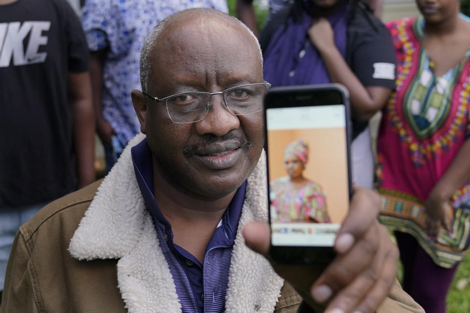 Sophonie Bizimana, a permanent U.S. resident who is a refugee from Congo, poses for a photo, Wednesday, Oct. 14, 2020, at his home in Kirkland, Wash., as he displays a cell-phone photo of his wife, Ziporah Nyirahimbya, who is in Uganda and has been unable so far to join him in the U.S. For decades, America admitted more refugees annually than all other countries combined, but that reputation has eroded during Donald Trump's presidency as he cut the number of refugees allowed in by more than 80 percent. (AP Photo/Ted S. Warren)