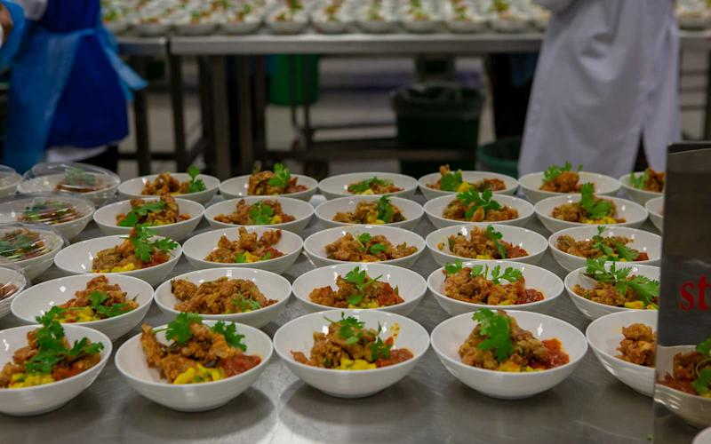 Hot dishes are prepared and plated to be loaded on aircraftfor upcoming flights. | Talia Avakian