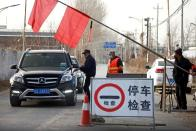 Volunteers stop a car at a checkpoint on a road leading into their village on the outskirts of Beijing