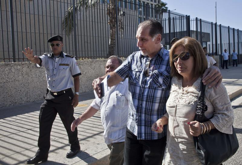 Rene Gonzalez, accompanied by his wife Olga Salanueva, leaves the U.S. Interests Section after starting paperwork to his renounce his U.S. citizenship in Havana, Cuba, Monday, May 6, 2013. Gonzalez, a Cuban spy who spent 13 years in a U.S. prison, renounced his American citizenship Monday, part of a deal that allows him to avoid returning to the United States to serve out the remainder of his probation. (AP Photo/Ramon Espinosa)