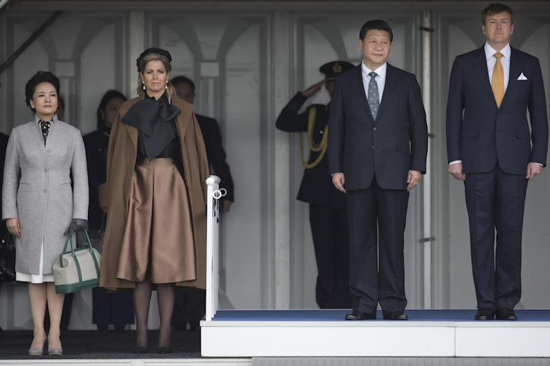 China's President Xi Jinping, second right, his wife Peng Liyuan, left, Dutch King Willem Alexander, right, and his wife Queen Maxima, second left, listen to the national anthems prior to the inspection of the honor guard upon Xi's arrival at Schiphol Amsterdam airport, Netherlands, Saturday March 22, 2014. Xi is on a two-day state visit ahead of the March 24 and 25 Nuclear Security Summit in The Hague. (AP Photo/Peter Dejong, Pool)