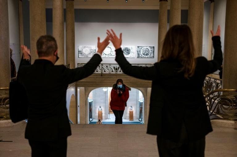 The Montreal Museum of Fine Arts' director Stephane Aquin (L) and curator Mary-Dailey Desmarais (R) cheer on the first guest to arrive for the re-opening on February 11, 2021