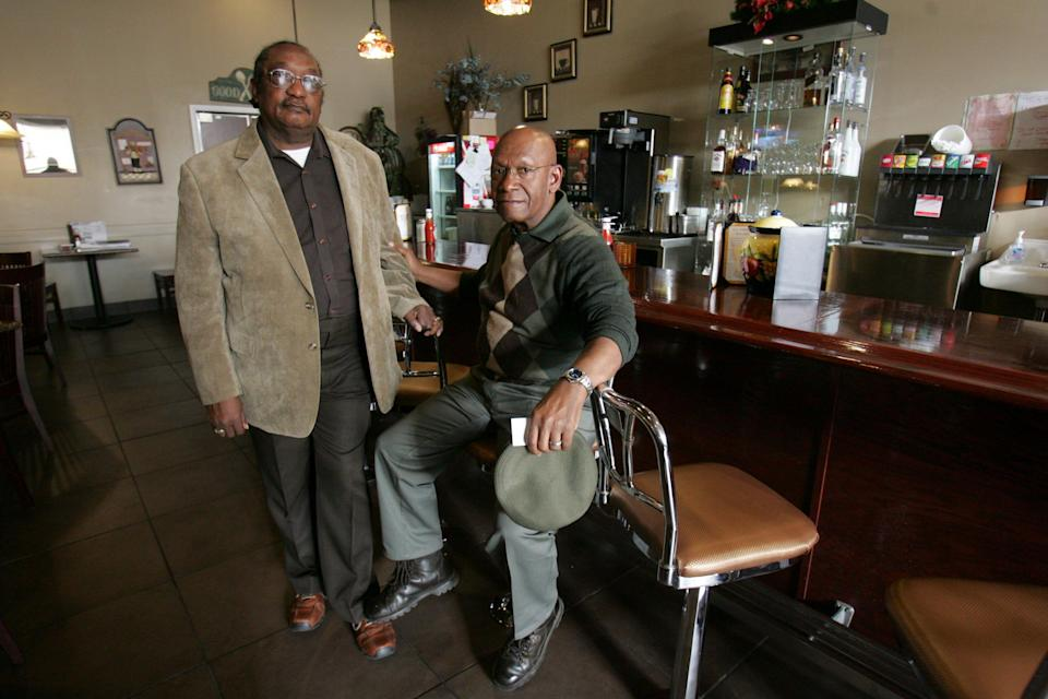 """In this March 5, 2009, file photo, the Rev. W. T. """"Dub"""" Massey, right, and Willie McLeod, left, pose at the counter where they were among the """"Friendship Nine"""" who were jailed during 1960s civil rights sit-ins."""